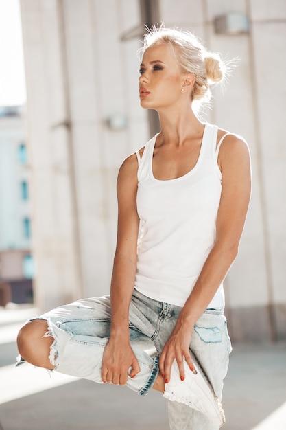 Retrato de uma linda garota loira bonita camiseta branca e calça jeans posando ao ar livre. linda garota de pé no fundo da rua Foto gratuita