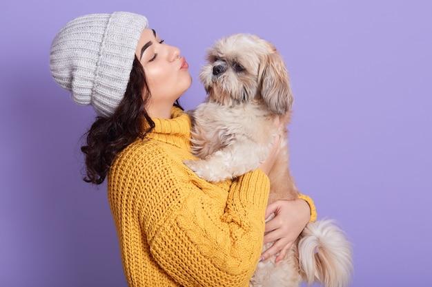 Retrato de uma linda garota mantendo a bela pequinês e quer beijá-lo Foto gratuita