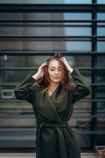 Retrato de uma linda garota ruiva caucasiana, posando no fundo de um arranha-céu. Foto Premium