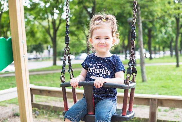 Retrato de uma linda garota sentada no balanço Foto gratuita