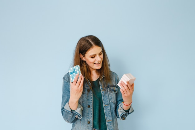 Retrato de uma linda jovem animado segurando um presente e feliz sobre fundo azul Foto Premium
