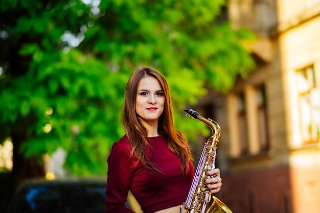 Retrato de uma linda jovem caminhando na rua com um saxofone Foto Premium