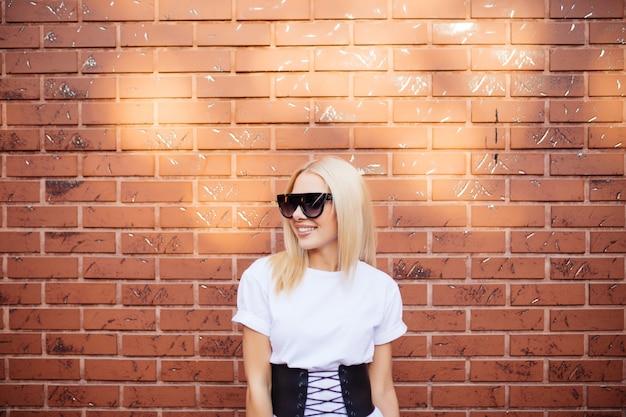 Retrato de uma linda jovem em óculos de sol vermelhos sobre uma parede de tijolo vermelho Foto gratuita