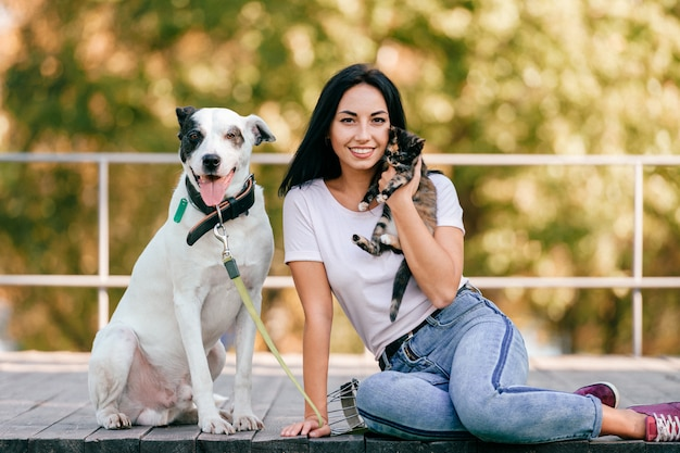 Retrato de uma linda jovem morena com gatinho e cachorro grande cão sentado ao ar livre no parque Foto Premium