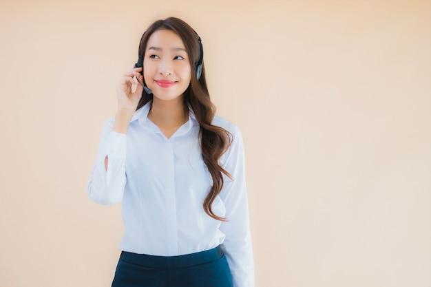 Retrato de uma linda jovem mulher de negócios asiática com fone de ouvido para call center Foto gratuita