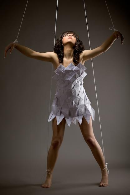 Retrato de uma linda jovem triste em um vestido de origami com os braços em movimento como uma marionete em um fundo preto Foto Premium