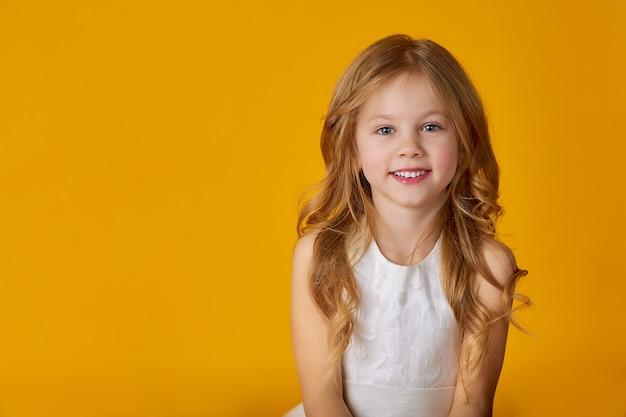 Retrato de uma linda menina de 6 anos em um vestido branco posando em um amarelo brilhante Foto Premium