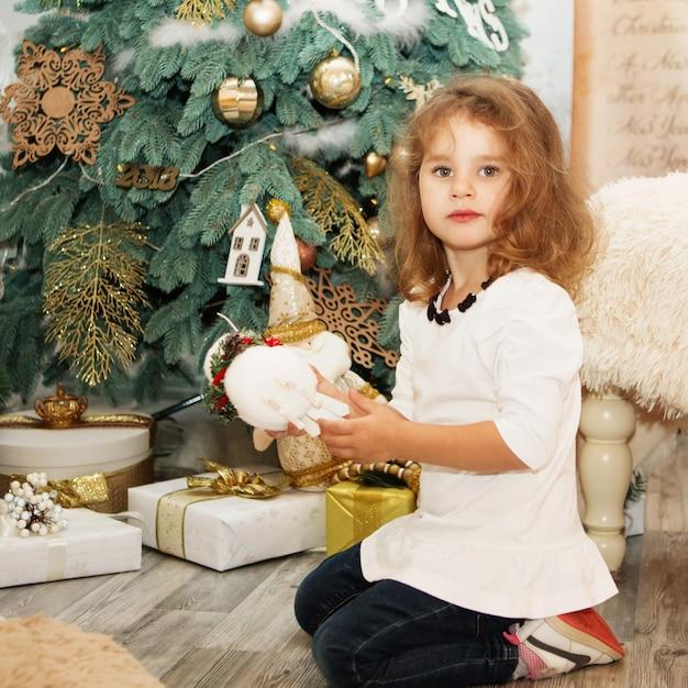 Retrato de uma linda menina entre as decorações de natal Foto Premium