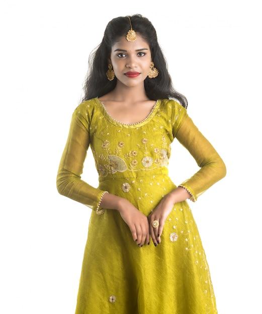 Retrato de uma linda menina indiana tradicional posando na parede branca Foto Premium