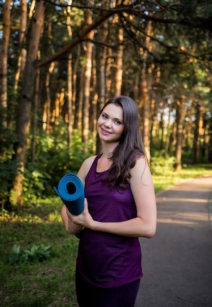 Retrato de uma linda menina morena com um tapete de ioga no caminho no parque Foto Premium
