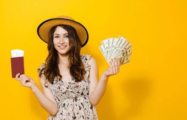 Retrato de uma linda menina morena feliz segurando notas de dinheiro viajar bilhetes e passaporte Foto Premium