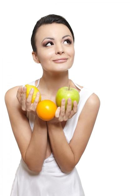 Retrato de uma linda menina sorridente feliz com frutas limão e maçã verde e laranja isolado no branco Foto gratuita