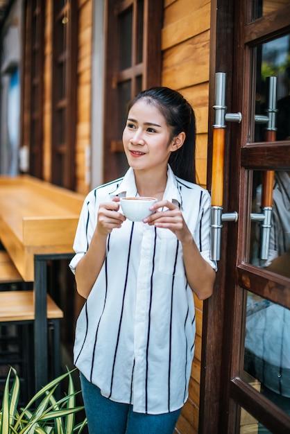 Retrato de uma linda mulher asiática relaxar no café Foto gratuita
