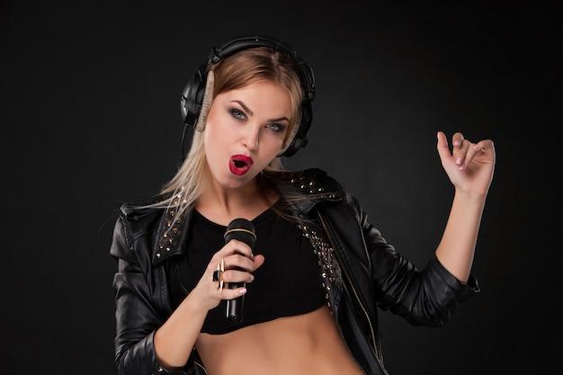 Retrato de uma linda mulher cantando no microfone com fones de ouvido na parede preta Foto gratuita