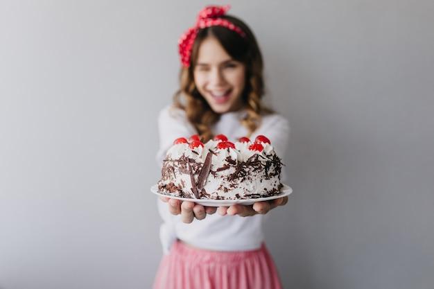 Retrato de uma linda mulher com bolo cremoso em primeiro plano. aniversariante bem humorada isolada. Foto gratuita