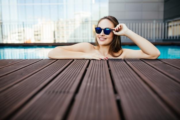 Retrato de uma linda mulher em óculos de sol, posando à beira da piscina, dia de verão, ao ar livre Foto gratuita