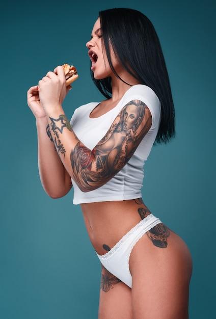 Retrato de uma linda mulher encantadora com tatuagens segurando um hambúrguer Foto gratuita