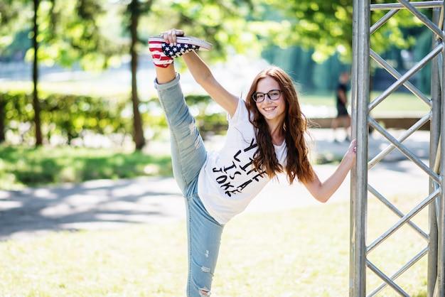 Retrato de uma linda mulher flexível fazendo split no parque em um dia ensolarado Foto Premium