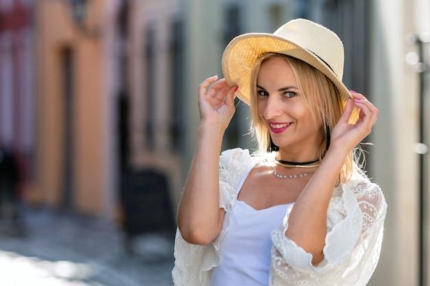 Retrato de uma linda mulher loira com chapéu de sol, vestido com roupas leves. menina na moda posando no fundo da rua Foto Premium