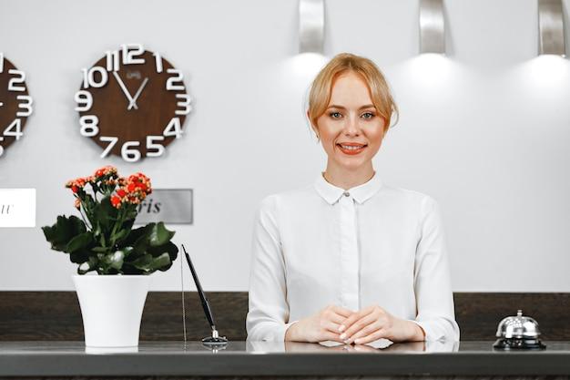 Retrato de uma linda mulher loira recepcionista de hotel close-up Foto Premium