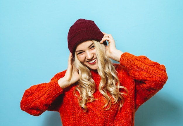 Retrato de uma linda mulher loira, vestindo um boné e está vestido com uma camisola vermelha e mostrando a moda se move sobre fundo azul Foto Premium