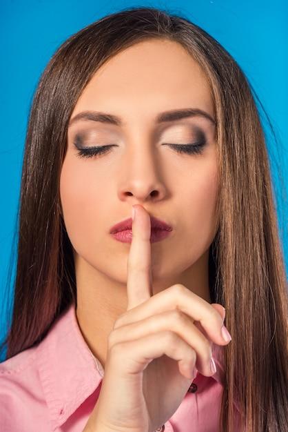 Retrato de uma linda mulher manter o dedo perto da boca. Foto Premium
