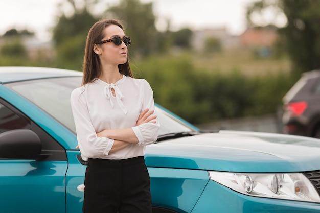 Retrato de uma linda mulher na frente de um carro Foto gratuita
