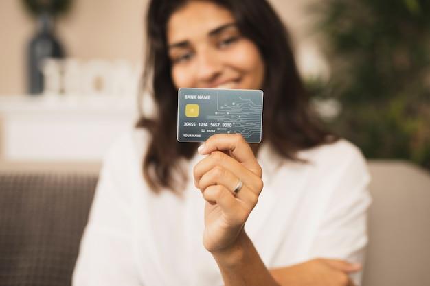 Retrato de uma linda mulher segurando um cartão de crédito Foto gratuita