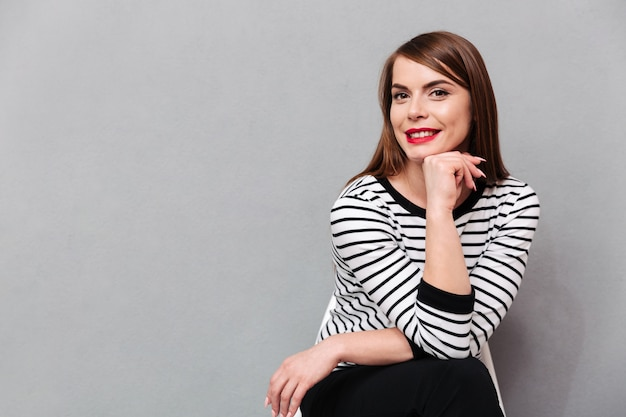 Retrato de uma linda mulher sentada na cadeira Foto gratuita