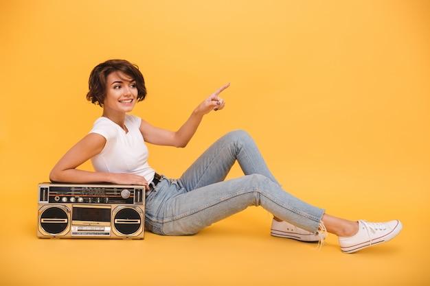 Retrato de uma linda mulher sorridente, sentado com toca-discos Foto gratuita