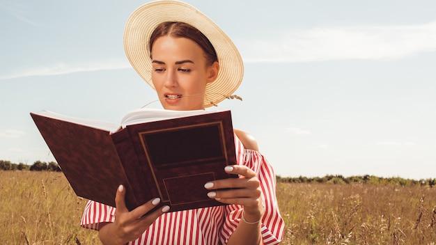 Retrato de uma linda senhora. lê um livro no campo. prepare-se para o ingresso na universidade. Foto gratuita