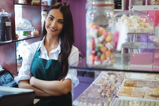 Retrato de uma lojista em um balcão de doces turcos Foto gratuita