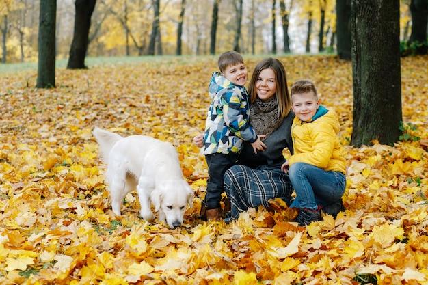 Retrato de uma mãe com dois filhos e um cachorro em um parque de outono Foto Premium