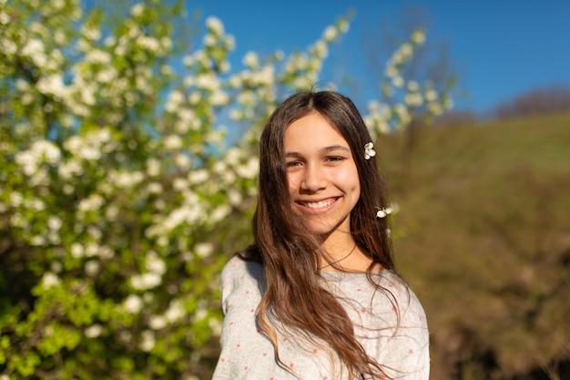 Retrato de uma menina adolescente bonita em um jardim de primavera verde florescendo Foto Premium