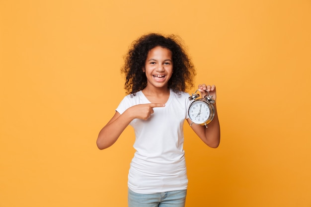 Retrato de uma menina africana, apontando o dedo no despertador Foto gratuita