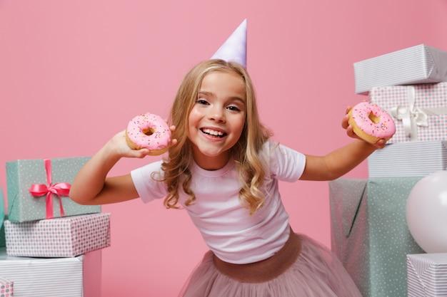 Retrato de uma menina alegre em um chapéu de aniversário Foto gratuita
