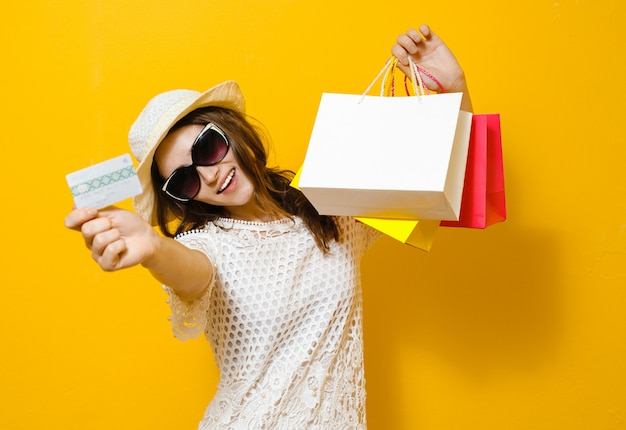 Retrato de uma menina alegre sorridente segurando sacolas de compras e mostrando o cartão de crédito sobre amarelo Foto Premium
