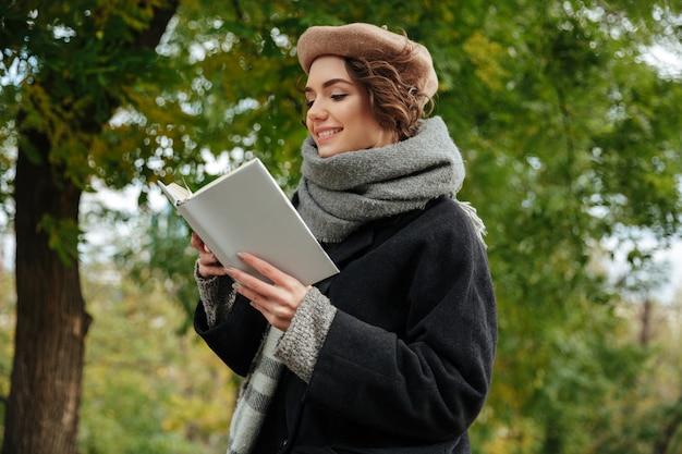 Retrato de uma menina alegre, vestida com roupas de outono lendo Foto gratuita