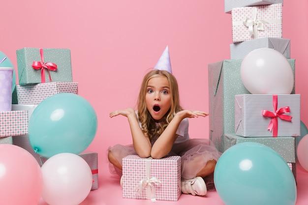 Retrato de uma menina animada em um chapéu de aniversário Foto gratuita