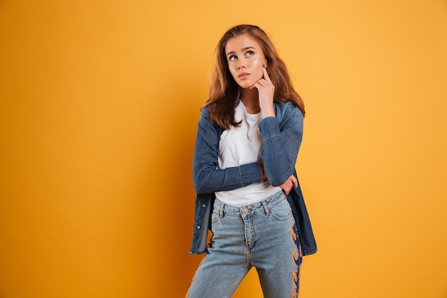 Retrato de uma menina bonita casual pensando e olhando para longe Foto gratuita