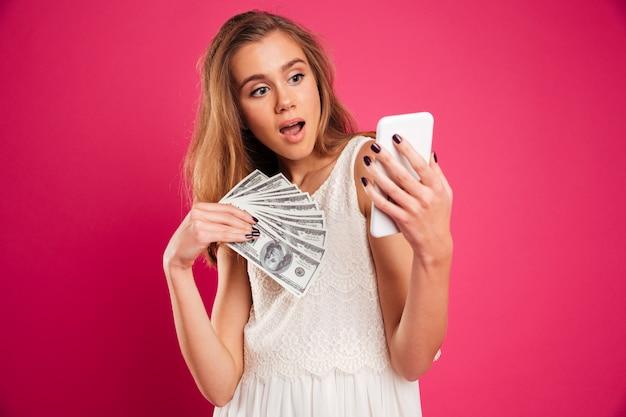 Retrato de uma menina bonita chocada segurando notas de dinheiro Foto gratuita