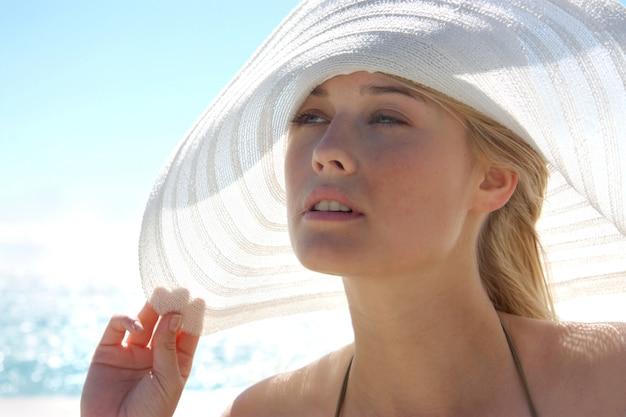 Retrato de uma menina bonita com chapéu no mar Foto Premium