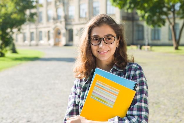 Retrato de uma menina bonita estudante em copos com livros. Foto Premium