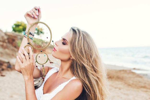 Retrato de uma menina bonita loira com cabelo comprido na praia. segura a ornamentação na mão e mantém os olhos fechados. Foto gratuita