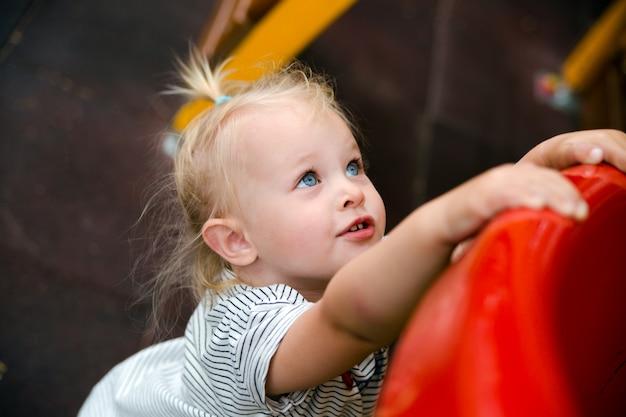 Retrato de uma menina brincando no playground. copie o espaço. Foto Premium
