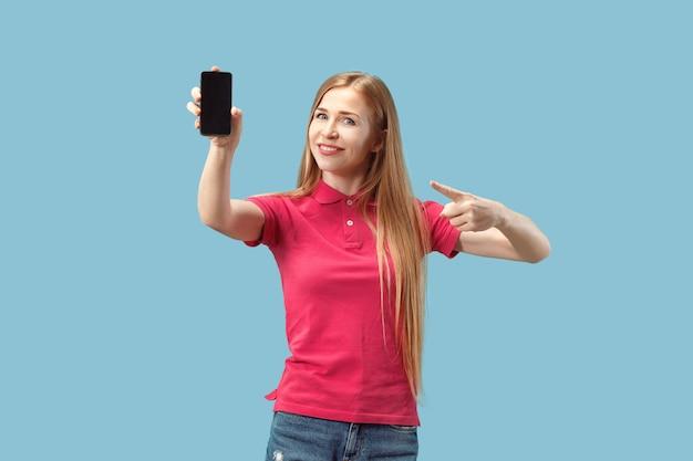 Retrato de uma menina casual confiante, mostrando o telefone móvel de tela em branco isolado sobre fundo azul Foto gratuita
