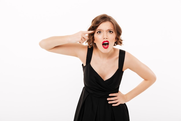 Retrato de uma menina com raiva, vestida de vestido preto Foto gratuita