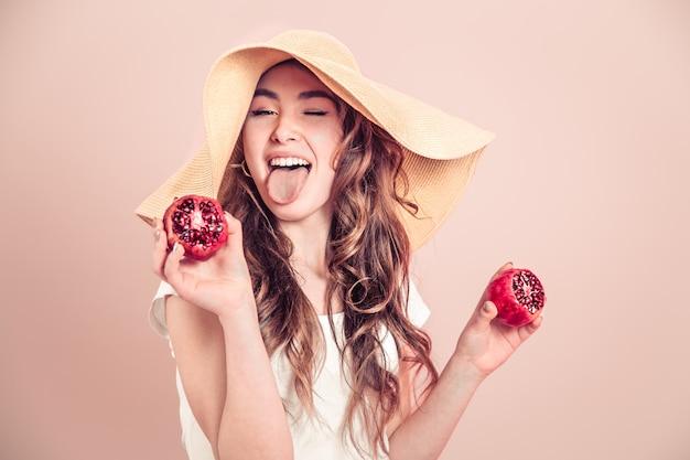 Retrato de uma menina com um chapéu de verão com frutas em uma parede colorida Foto gratuita