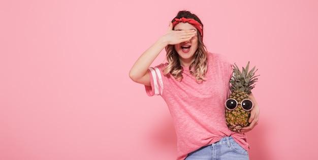 Retrato de uma menina com um olho fechado em um fundo rosa Foto gratuita