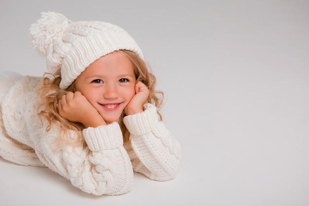 Retrato de uma menina de cabelos cacheados em um chapéu branco de malha de inverno Foto Premium